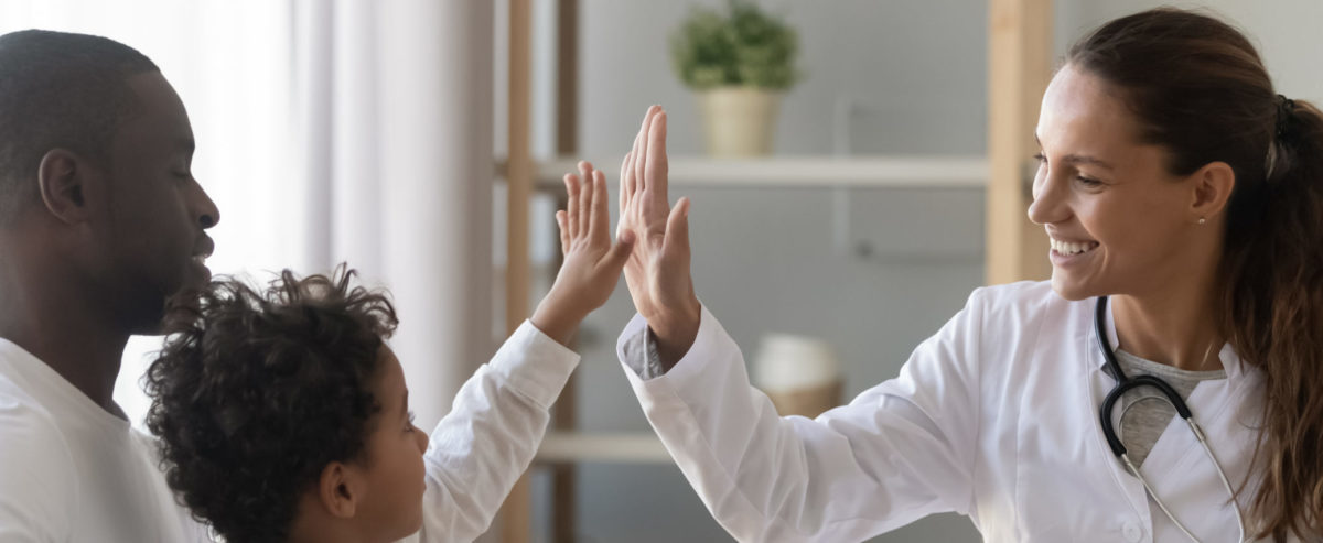 Boy greeting woman doctor during visit meeting in clinic